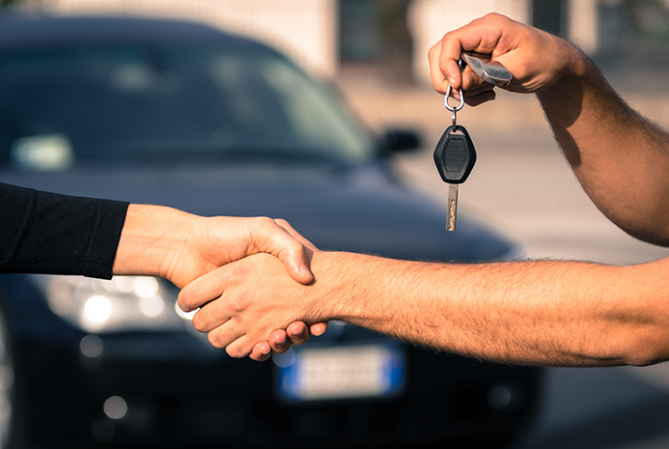 Two people shaking hands, one is handing car keys to the other.