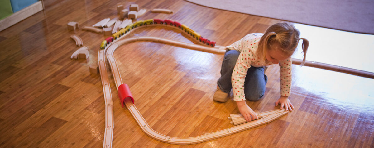 LIttle girl playingn with wooden train tracks