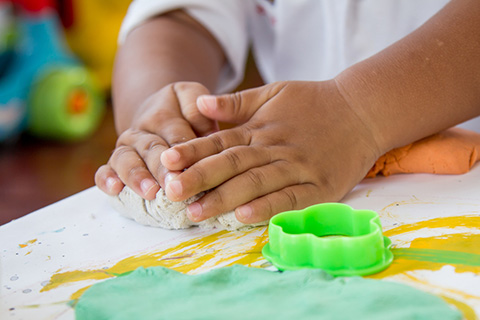 Hands of a child playing with Playdoh