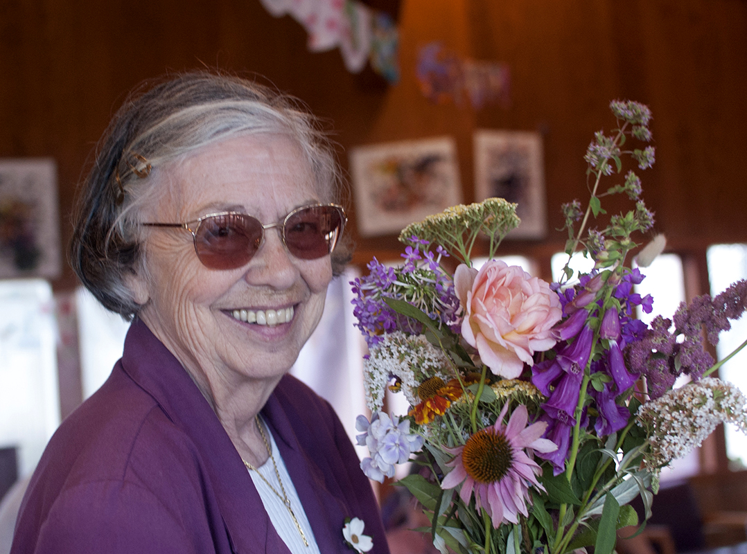 Woman smiling standing next to flowers
