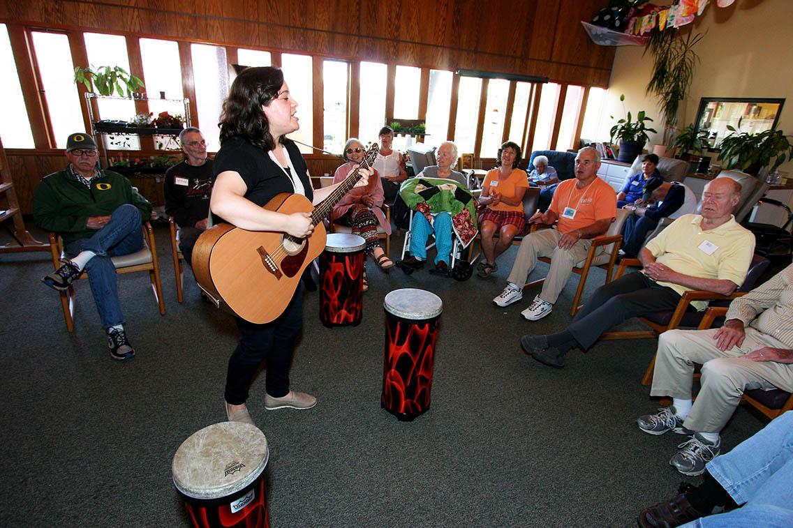Group of people singing, woman playing guitar