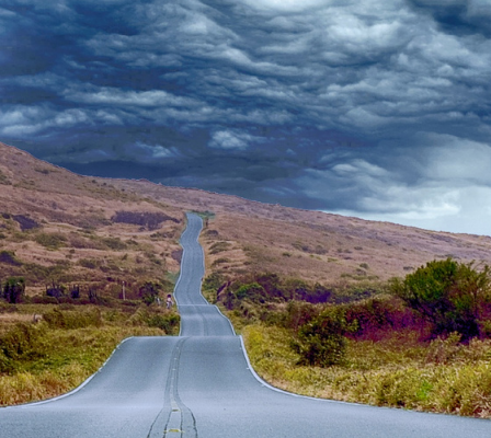 road going into the distance with dark clouds in the sky